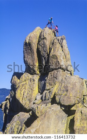 Team of climbers struggle to the summit of a challenging mountain. - stock photo