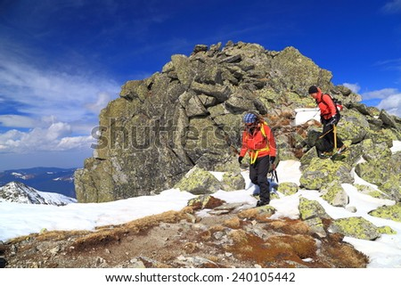 Team of climbers traversing rocky boulders on the mountain trail during winter  - stock photo