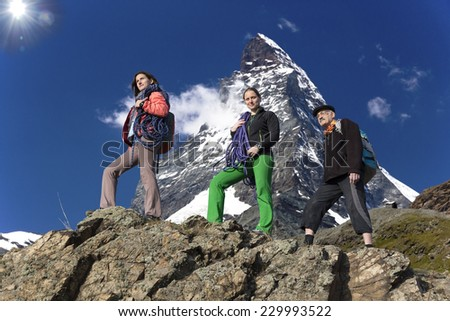 Team of climbers walks against alpine background. Further and daughters walk on the mountain ridge. High alpine landscape on the background  - stock photo