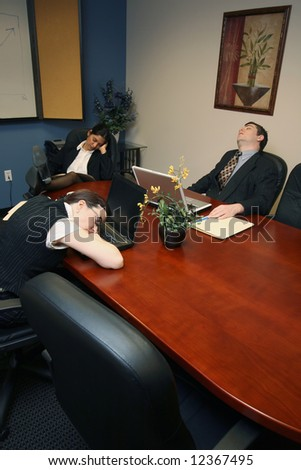 Team of colleagues fast asleep in a meeting room - stock photo