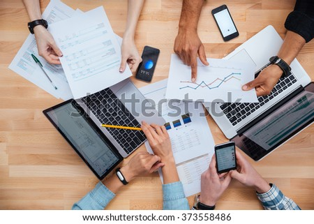 Team of colleagues working for financial report using laptops and smartphones