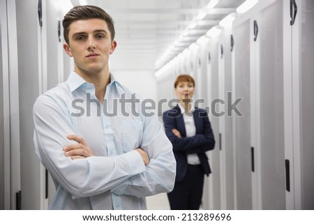 Team of computer technicians looking at camera in large data center - stock photo