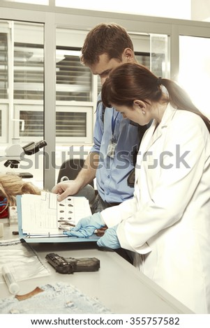 Team of criminologists working in laboratory - stock photo