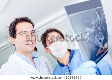 Team of doctors looking at an x-ray at the hospital - stock photo