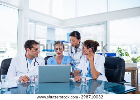 Team of doctors looking at laptop in the meeting room - stock photo