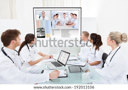 Team of doctors looking at projector screen in video conference meeting at hospital - stock photo