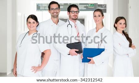 Team of doctors standing in hospital corridor - stock photo