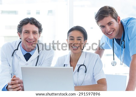 Team of doctors working on laptop and smiling at camera in medical office - stock photo