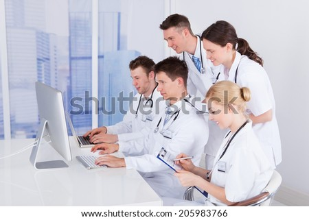 Team of doctors working together on computer in hospital - stock photo
