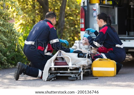 team of emergency medical staff rescuing patient - stock photo