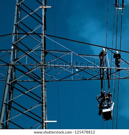 Team of engineers repairing a high voltage wire. - stock photo
