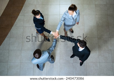 team of four businesspeople with folded hands, a symbol of teamwork - stock photo