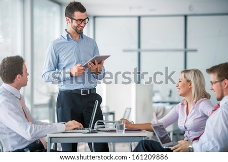 Team of four corporate people meeting in office