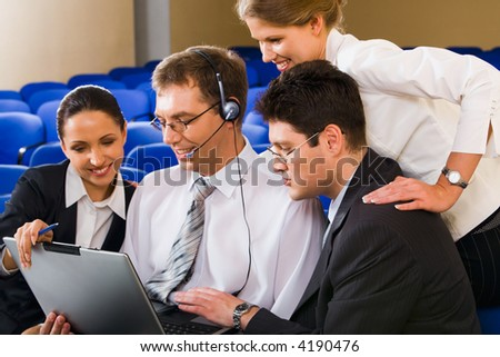 Team of four young business people gathered together around the laptop discussing a plan in the hall