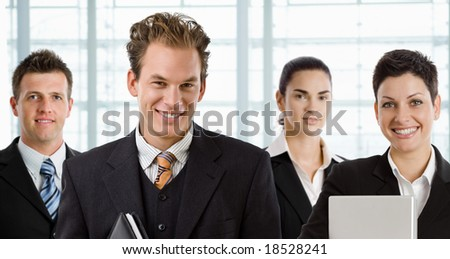 Team of happy business people, smiling businessman in front. - stock photo