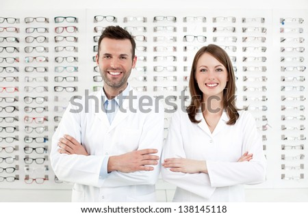 Team of happy opticians optometrists standing in optical shop