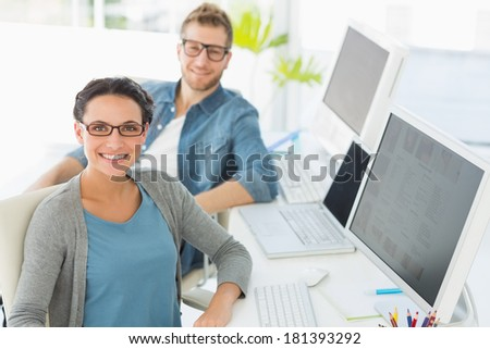 Team of happy young designers looking at camera in creative office - stock photo
