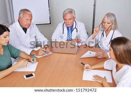 Team of many doctors talking in a group meeting - stock photo