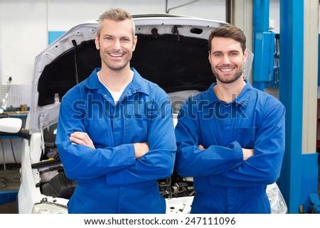 Team of mechanics smiling at camera at the repair garage - stock photo