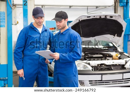 Team of mechanics talking together at the repair garage
