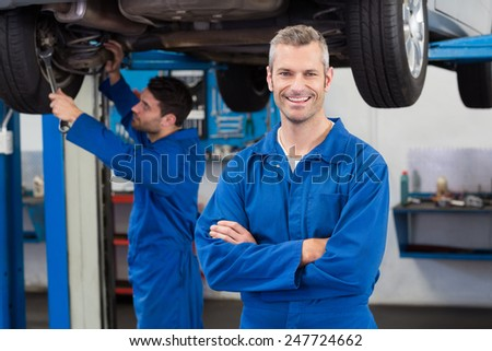 Team of mechanics working together at the repair garage - stock photo