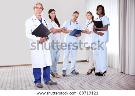 Team of medical professionals lead by mature happy doctor holding file looking at camera - Smiling. - stock photo