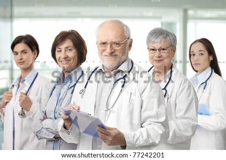 Team of medical professionals lead by senior white haired doctor looking at camera, smiling.?