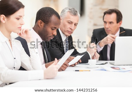 Team of multi ethnic business people discussing work - stock photo