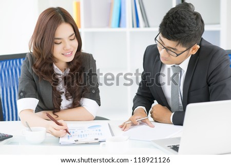 Team of office workers discussing possible strategic movements and analyzing statistics - stock photo