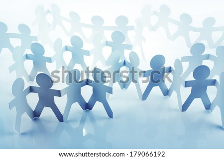 Team of paper doll people holding hands - stock photo