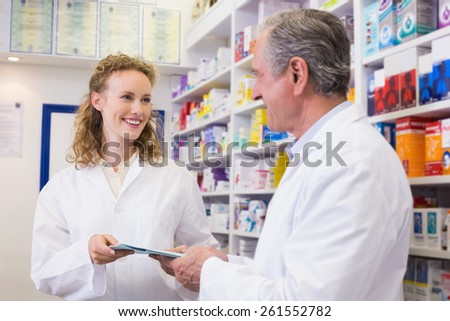 Team of pharmacist holding clipboard at hospital pharmacy