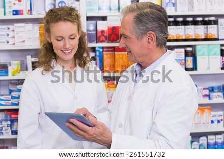Team of pharmacist looking at tablet pc at hospital pharmacy - stock photo