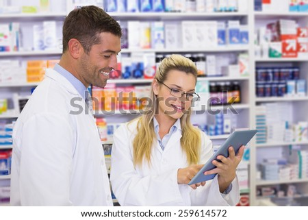 Team of pharmacists looking at laptop at the hospital pharmacy