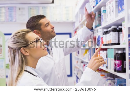 Team of pharmacists looking at medicine at the hospital pharmacy - stock photo