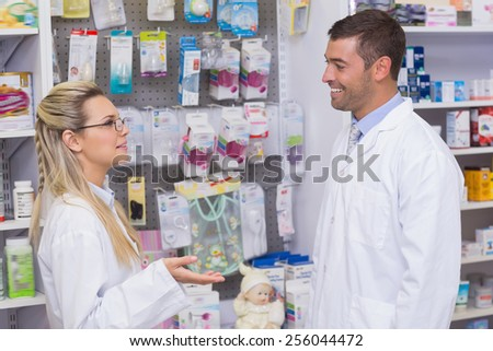 Team of pharmacists smiling and talking at the hospital pharmacy - stock photo