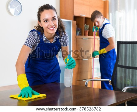 Team of positive smiling professional cleaners dusting in ordinary office - stock photo
