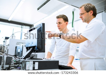 Team of researchers carrying out experiments in a lab (shallow DOF; color toned image) - stock photo