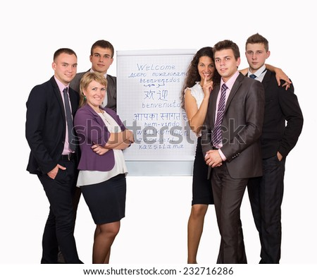 "Team of six business consultants welcomes participants of conference. Six business looking people stay next to flip chart with ""WELCOME"" sign written in many languages"