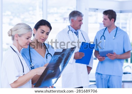Team of smiling doctors discussing in medical office - stock photo