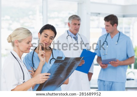 Team of smiling doctors discussing in medical office