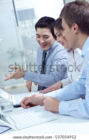 Team of smiling young office workers sitting at office table and working on laptop together