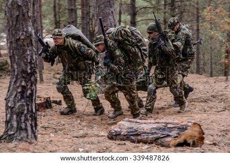 Team of soldiers evacuate wounded soldier on a stretcher from battlefield in forest/Evacuation of wounded soldier - stock photo