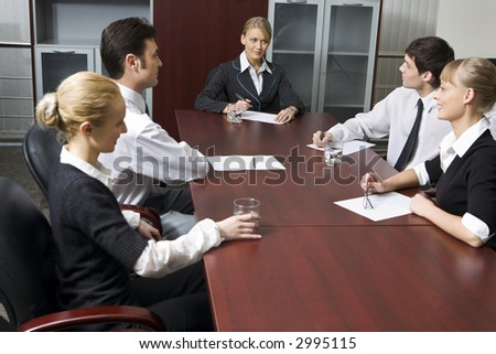 Team of successful business people are sitting at the table and discussing - stock photo