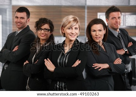 Team of successful happy businesspeople standing in office, businesswoman in front smiling. - stock photo