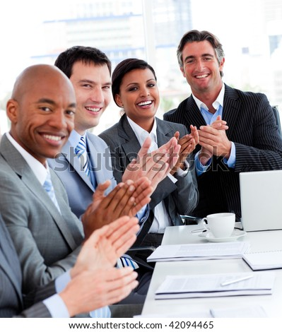 Team of successful multi-ethnic business people applauding in a conference - stock photo