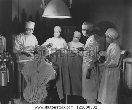 Team of surgeons perform operation - stock photo