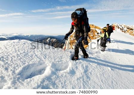 Team of three alpinists climbing a mountain - stock photo
