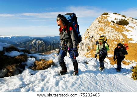 Team of three alpinists climbing a mountain - stock photo