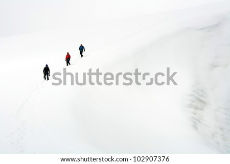 Team of three alpinists climbing a mountain during foggy weather - stock photo