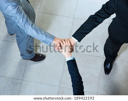 team of three businessmen clasped her hands together, a symbol of teamwork - stock photo